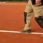 Tennislinierung Neuverlegung -Andrücken der Spannlinie in die Ziegelmehldeckschicht